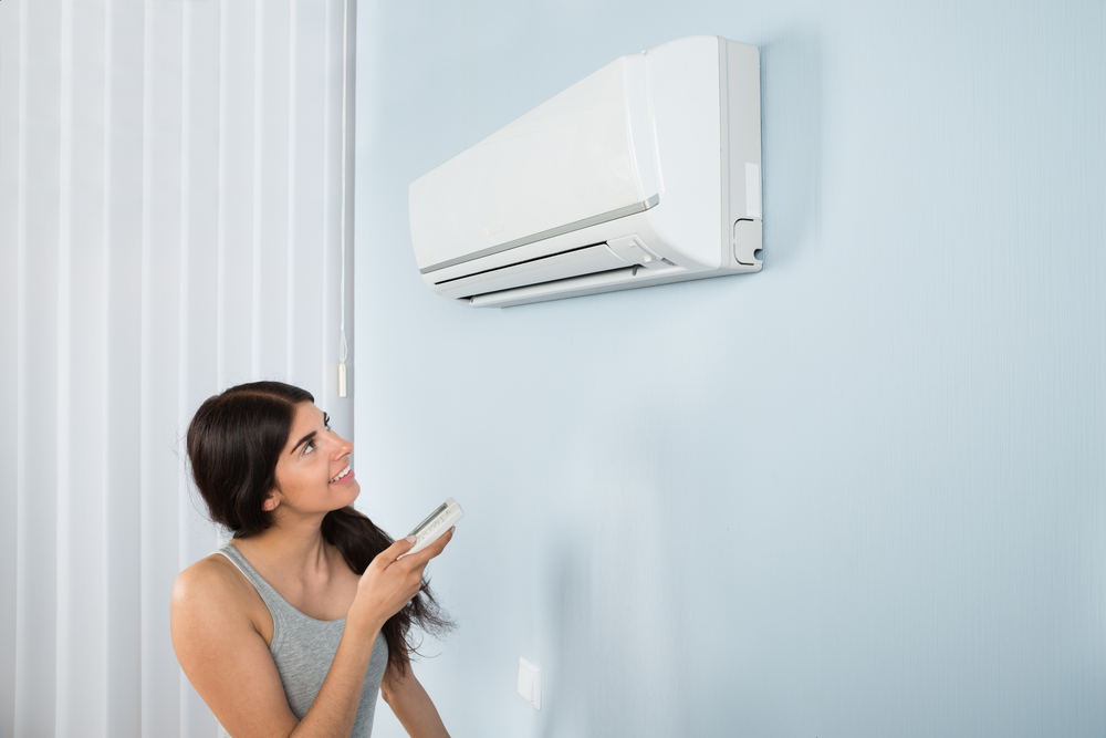 a woman turns on her wall mounted AC unit in San Diego