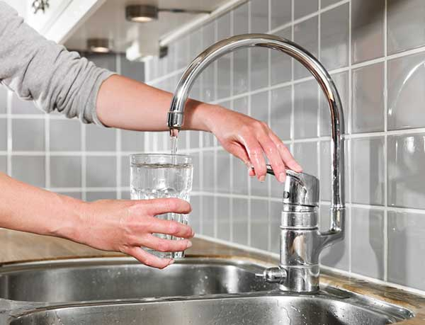 A person fills a cup with San Diego tap water.